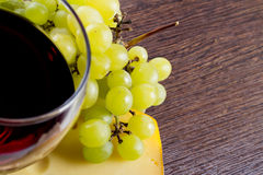 Glass of wine copy-space. Food closeup background. Glass of wine with grapes and piece of cheese copy-space royalty free stock photos