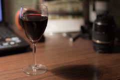 A glass of wine on the desk stock images