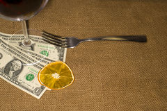 Glass of wine, a dried orange slice, fork and a few bills on th Royalty Free Stock Image