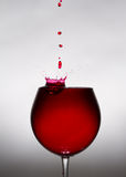 A glass of wine and a drop falling into it Royalty Free Stock Photography