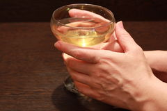 A glass of wine in female hands. On the table royalty free stock photo