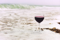 Glass of wine in the foam of the sea on the shore. Glass with red wine in a white sea foam on the beach. sea pebbles in the water. In the background, emerald royalty free stock photo