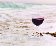 Glass of wine in the foam of the sea on the shore. Glass with red wine in a white sea foam on the beach. sea pebbles in the water. In the background, emerald stock photos
