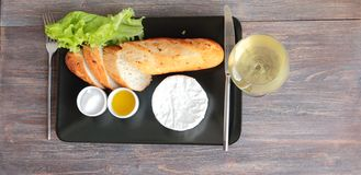 Glass of wine, french bread, soft cheese, honey, salt on black plate Stock Photos