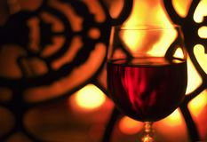Glass of wine in front of the fireplace Stock Images