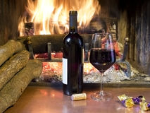 A glass of wine in front of a fireplace. Celebrate with a glass of wine, a bottle, in front of a fireplace Stock Image