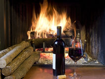 A glass of wine in front of a fireplace. Celebrate with a glass of wine, a bottle, in front of a fireplace Royalty Free Stock Image