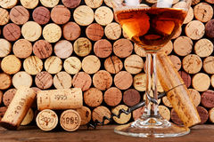 Glass of Wine  in Front of a Wall of Used Corks. Closeup of a wineglass in front of a wall of used corks. An antique cork screw and dated corks are adjacent to Royalty Free Stock Photography