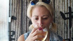 Glass of wine with girl. Smiling caucasian modern woman drinking white sparkling wine in an asian restaurant. Defocused background in slow motion. Lifestyle