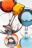 Glass wine glasses with multicolored liquid on a white backgroun Stock Image
