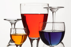 Glass wine glasses with multicolored liquid on a white background. Glass wine glasses with multicolored liquid (blue, yellow, red) on a white background Stock Photos