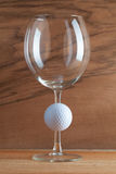 Glass of wine and golf ball Stock Photography