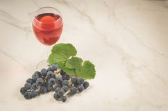 Glass of wine and grape/glass of wine and grape on a white marble, copy space royalty free stock photos