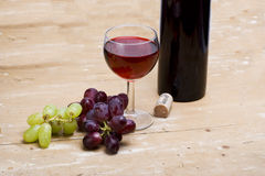 Glass of wine and grapes. A bottle of red wine with filled glass and fresh grapes on wooden table stock photo