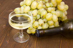 Glass of wine with grapes and bottle Stock Image