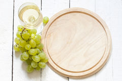 Glass of wine and grapes with empty cutting board Stock Photo