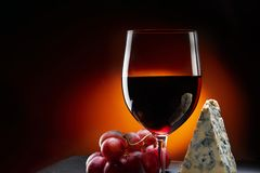 Glass of wine with grapes and a piece of cheese with mold. stock photo