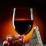 Glass of wine with grapes and a piece of cheese with mold. Orange background. stock images