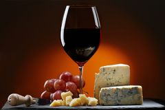 Glass of wine with grapes and a piece of cheese with mold, Parmesan cheese and cheese knife. stock photos