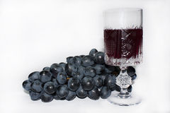 Glass of wine and grapes. On the white background Royalty Free Stock Images