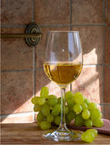Glass of wine and grapes. In the wooden table Stock Photo