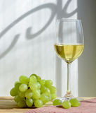 Glass of wine and grapes. In the wooden table Stock Photography
