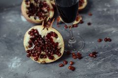 A glass of wine on a gray background among pomegranates. Close pomegranate and red pomegranate seeds royalty free stock photos