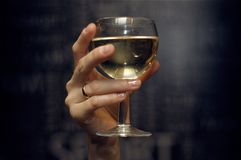 Glass of wine in hand on dark background royalty free stock photos