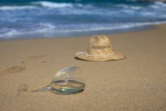 A glass of wine and a hat in the sand on the seashore. A glass of wine in the sand and straw hat on the beach. horizontal stock photography