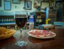 Glass of wine and jamon plate Stock Photos