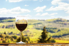 Glass of Wine on a Ledge Overlooking Vineyards in Chianti Italy. A glass of red Chianti wine resting on the ledge of a patio outdoors with the beautiful Italian stock photography