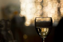 A glass of wine on a lighted background royalty free stock photography