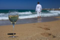 Glass of wine, and men's footprints on the beach closeup. Horizontal royalty free stock photos