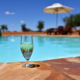 Glass of wine near swimming pool Royalty Free Stock Photography