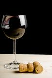 Glass of wine near two cork on old wood Stock Images