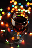 Glass of wine in new year. Eve with garlands Royalty Free Stock Photography