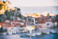 Glass of wine with Omis Riviera view, relax seascape background, Croatia. Glass of wine with Omis Riviera view, relax seascape background in soft sunset light royalty free stock photo