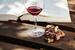Glass with wine and pieces of chocolate near open book. Glass with red wine and pieces of chocolate with nuts and raisins stands on wooden bar on background of Stock Images