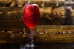Glass with wine pouring with liquid with splashes and drops of water. Wineglass filling with water with splashes on dark Royalty Free Stock Image