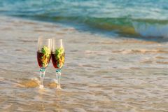 Glass of wine in the rays of the sunset. Glass on the sand. Romantic evening on the island. Concept of leisure and travel. Beautiful glass with wine of the royalty free stock image