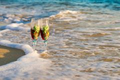 Glass of wine in the rays of the sunset. Glass on the sand royalty free stock image