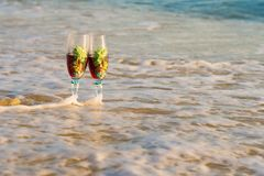 Glass of wine in the rays of the sunset. Glass on the sand stock photography
