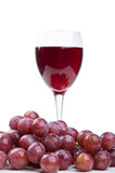 A glass of wine and red grapes Royalty Free Stock Images