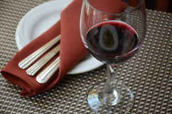 Glass of wine. A glass of red wine next to utensils on plate on the table in a restaurant royalty free stock photography