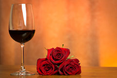 Glass of wine. A glass of wine and red roses stock photos