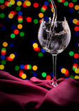 Glass of wine on red silk Royalty Free Stock Images