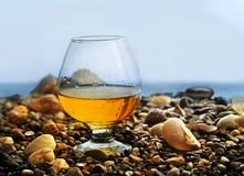 A glass of wine on the stones on the beach. A glass of wine on the rocks with drops on the seashore royalty free stock photo