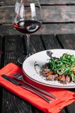 Glass of wine and salad with warm veal Stock Photos