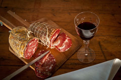 A glass of wine with salami from above. Delicious Mediterranean snack: red wine with salami, landscape, seen from above Royalty Free Stock Photos