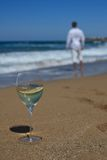 Glass of wine on the sand closeup and a man near the sea. A glass of wine on the sand close-up and a man near the sea. vertical Stock Images